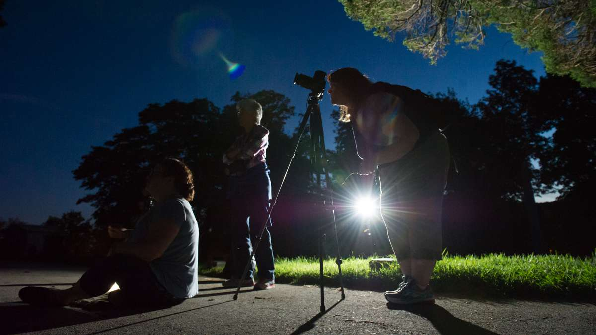 After dark, a photographer composes her subject.
