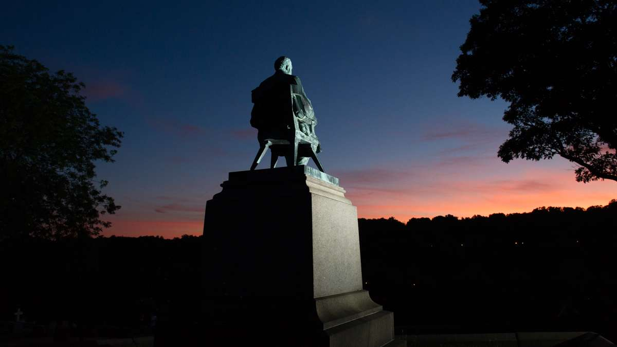 A statue of W. E. Hughes sits atop his burial plot facing the Schuylkill River at sunset.