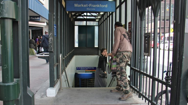 A SEPTA rider stops to give some change to a man panhandling outside the 11th Street station. (Emma Lee/WHYY)