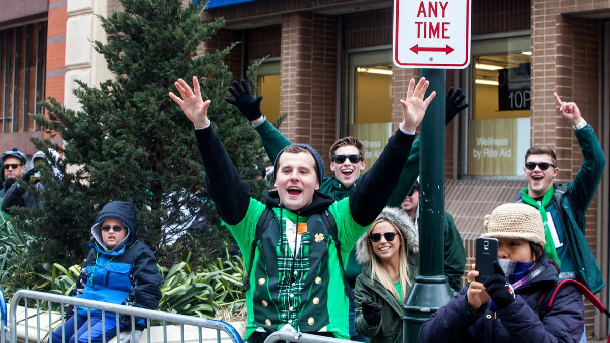 Spectators cheer during the Saint Patrick's Day Parade down Market Street Sunday afternoon.