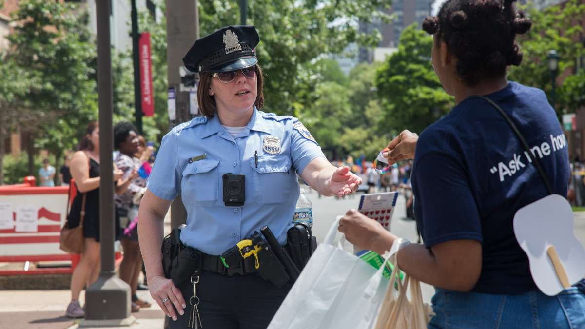 A marcher gives a Philadelphia police officer a pride bracelet at the 2017 Philadelphia Pride Parade, Sunday, June 18, 2017.