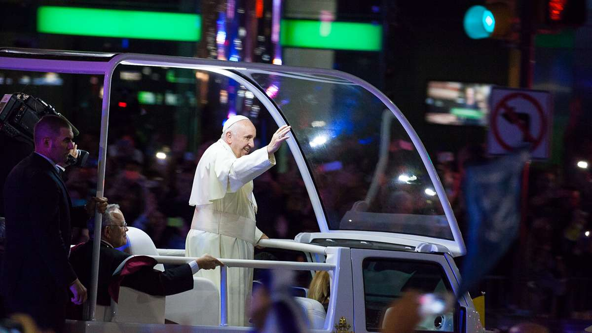 Festival of Families: Pope Francis waves to the crowd at 15th and JFK Boulevard during Saturday's parade. (Brad  Larrison/for NewsWorks)