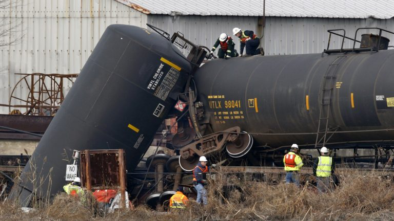 In this Friday, Nov. 30, 2012 file photograph, officials examine a derailed freight train tank car in Paulsboro, N.J., after a train derailed and several tanker cars carrying hazardous materials toppled from a bridge and into a creek. (Mel Evans/AP Photo, file)