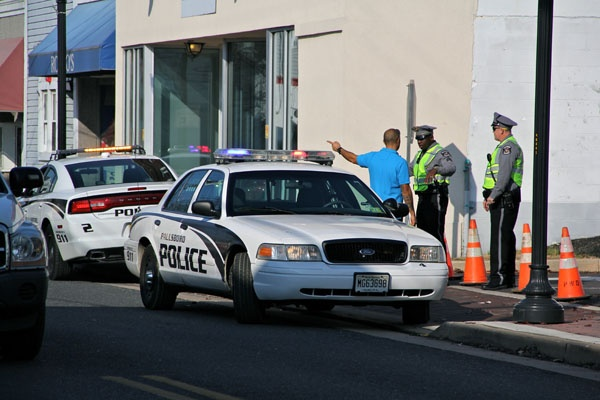 <p>Paulsboro police on Delaware Avenue keep residents and business owners away from a 12-block area evacuated because of a chemical spill from a derailed train. (Emma Lee/for NewsWorks)</p>