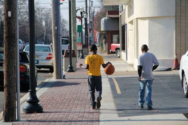 <p>DeAndre Gardner and William Graham head out to play basketball on Broad Street in Paulsboro. Because of a chemical spill, residents were warned to stay indoors and schools were closed, but by noon the warning had been lifted. (Emma Lee/for NewsWorks)</p>