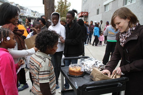 "<p><p>Kristyn Stewart, director of PCAT, gives the winners of the ""cake walk"" game a free homemade cake. (Trenae V. McDuffie/for NewsWorks)</p></p>"