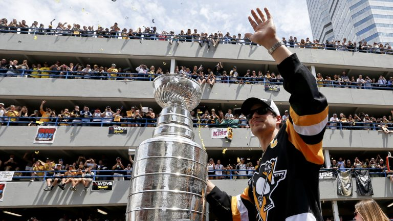 Pittsburgh Penguins' Sidney Crosby waves to the crowd while holding onto the Stanley Cup while riding along the victory parade route in Pittsburgh, Pa., Wednesday, June 15, 2016. The Penguins defeated the San Jose Sharks on Sunday, June 12 to win the NHL hockey championship. (AP Photo/Keith Srakocic)