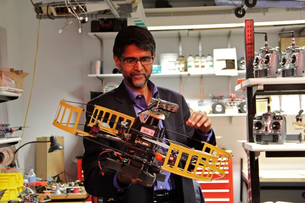 <p>Professor Vijay Kumar holds a large flying robot developed at the University of Pennsylvania's Grasp  Laboratory. (Emma Lee/for NewsWorks)</p>