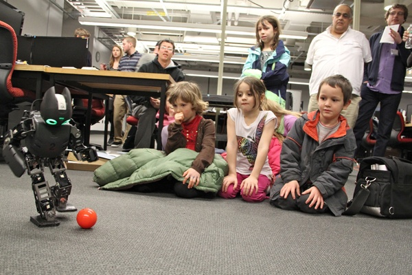 <p>Children watch Lucy, a soccer playing robot, during a break in the Y Prize competition at the University of Pennsylvania. (Emma Lee/for NewsWorks)</p>