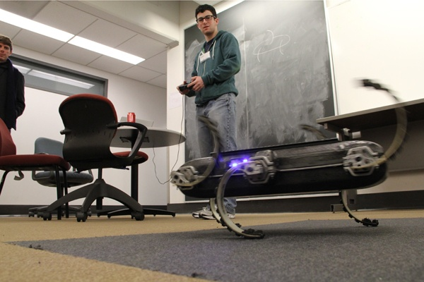 <p>Penn student Justin Starr controls a hexapedal robot. Inspired by insect movement, the six-legged robot can move over uneven terrain. (Emma Lee/for NewsWorks)</p>