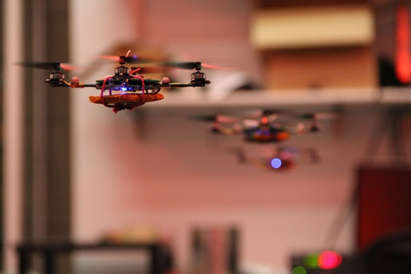 <p>Tiny quadrotor robots hover in formation in the Grasp robotics laboratory at the University of Pennsylvania. (Emma Lee/for NewsWorks)</p>