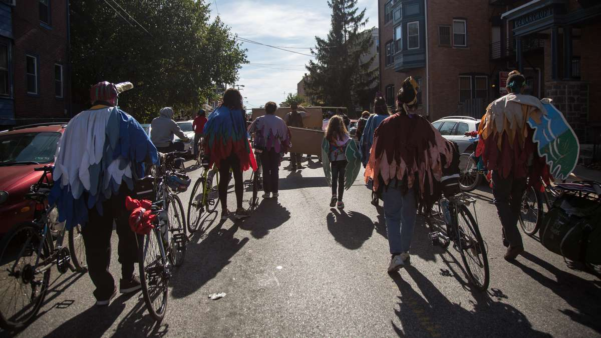 Members of the Neighborhood Bike Works delegation march as birds for the 17th annual Peoplehood parade in West Philadelphia, Oct. 29, 2016.
