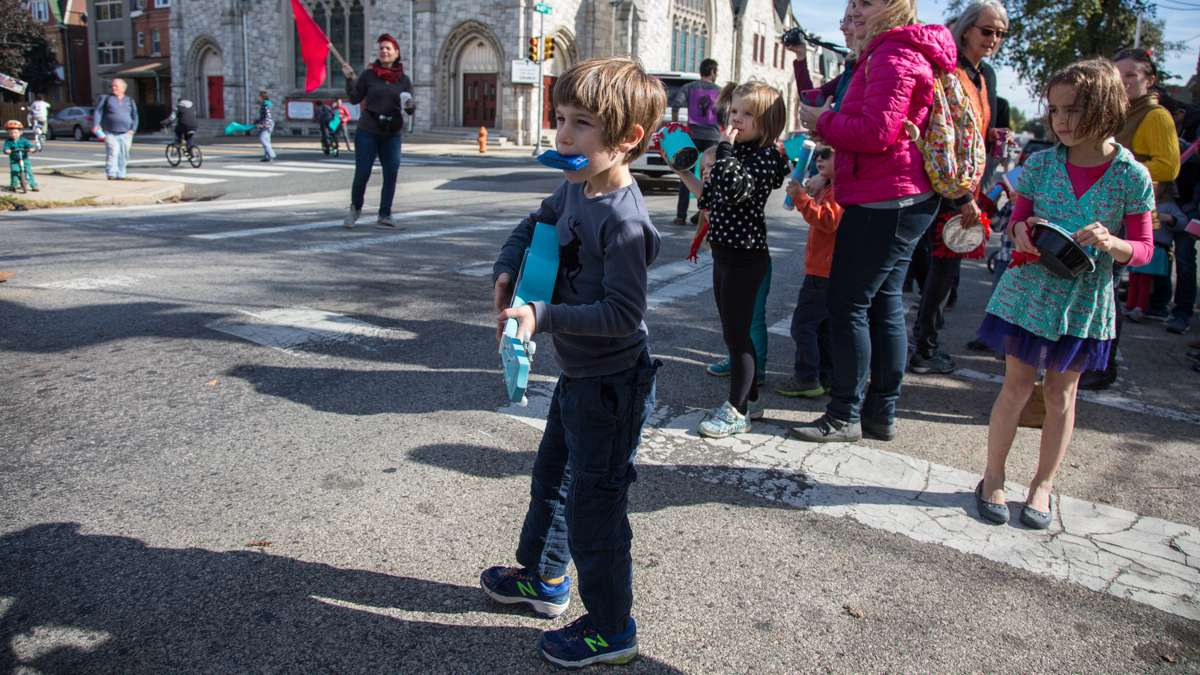 Kids from Children's Community School join the parade halfway through the route with noise makers. (Emily Cohen for NewsWorks)