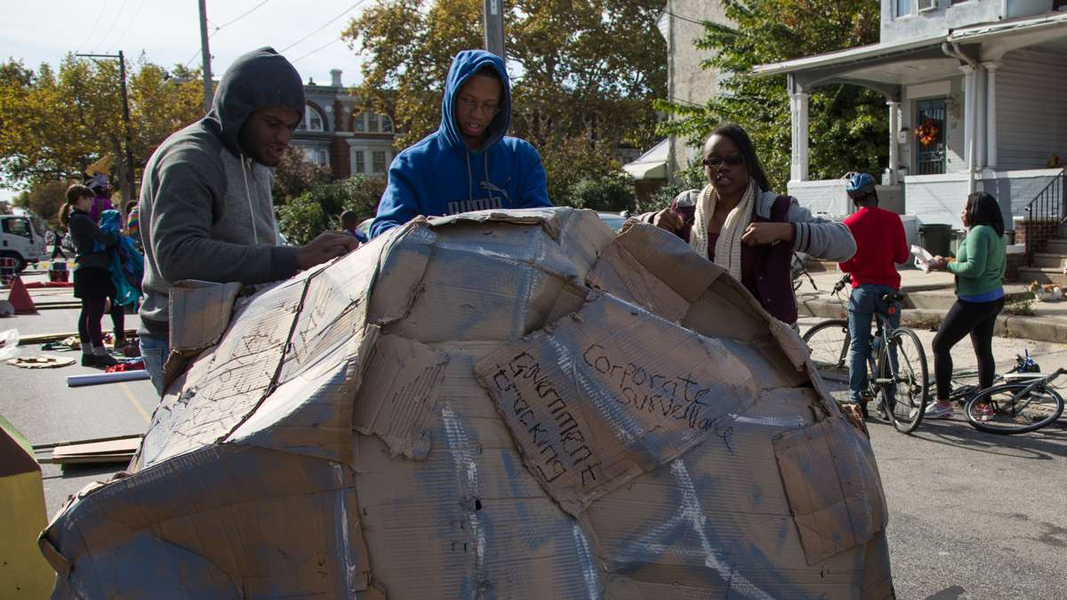 Teenagers from the Youth Volunteer Corps cover a cardboard boulder with different types of injustice before the start of the 17th annual Peoplehood parade in West Philadelphia, October 29th 2016. (Emily Cohen for NewsWorks)