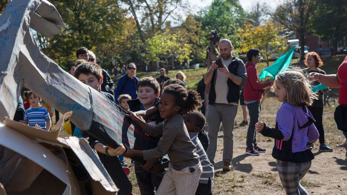 Children use a paper maché hammer to smash the boulder of injustice at the conclusion of the 17th annual Peoplehood parade Oct. 29, 2016. (Emily Cohen for NewsWorks)