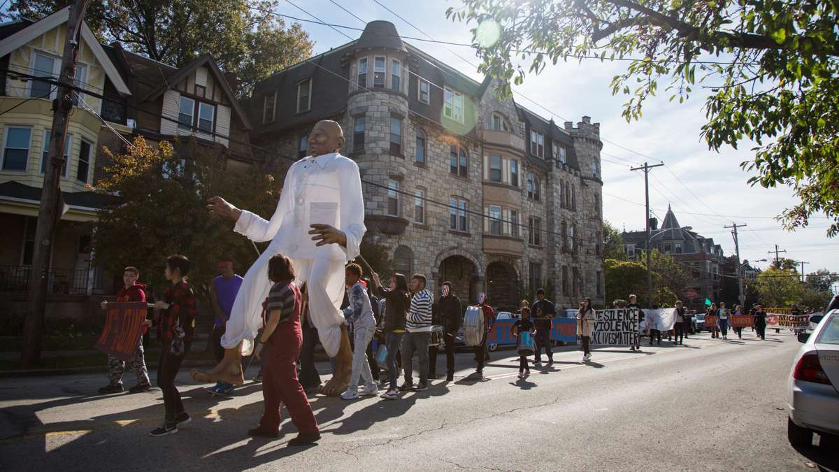 Social justice advocates march in the 17th annual Peoplehood parade Oct. 29, 2016, behind a giant puppet symbolizing the power of communities working together. (Emily Cohen for NewsWorks)