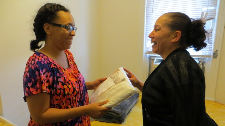 Carmen Perez, of the Children's Hospital of Philadelphia's Community Asthma Prevention Program, gives Victoria Harris mattress covers and a special pillowcase for her children. (Taunya English/WHYY)
