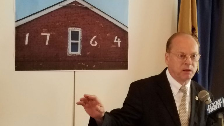 Chris Perks, president of the Camden County Historical Society, stood in front if an image of the Hugg-Harrison house. He filed a lawsuit against the NJDOT. (Peter Crimmins/WHYY)