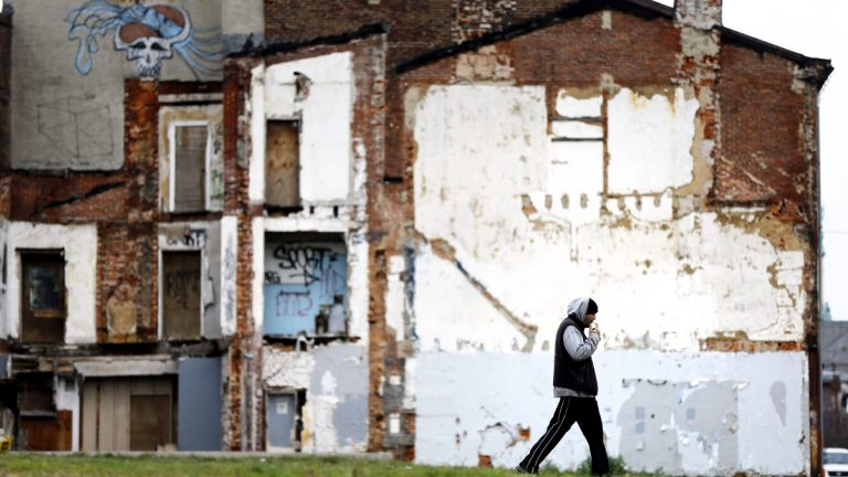 A man walks through a vacant lot where the impression on a demolished home remains on a standing building in the Northern Liberties neighborhood of Philadelphia. (AP Photo/Matt Rourke)