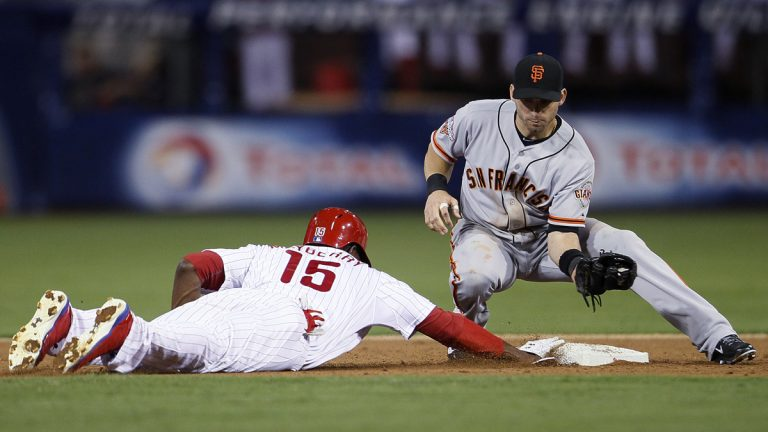 Philadelphia Phillies' John Mayberry, left, dives back to second base where San Francisco Giants' Marco Scutaro is waiting on a pick-off attempt during the seventh inning of a baseball game Tuesday, July 30, 2013, in Philadelphia. Mayberry made it back safely. The Phillies won 7-3. (AP Photo/Tom Mihalek)