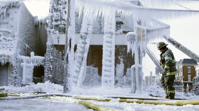A Philadelphia firefighter walks near the scene of an overnight blaze in west Philadelphia, where ice has formed from the water used to fight the fire. Bone-chilling, single digit temperatures have gripped the region. (AP Photo/Jacqueline Larma)
