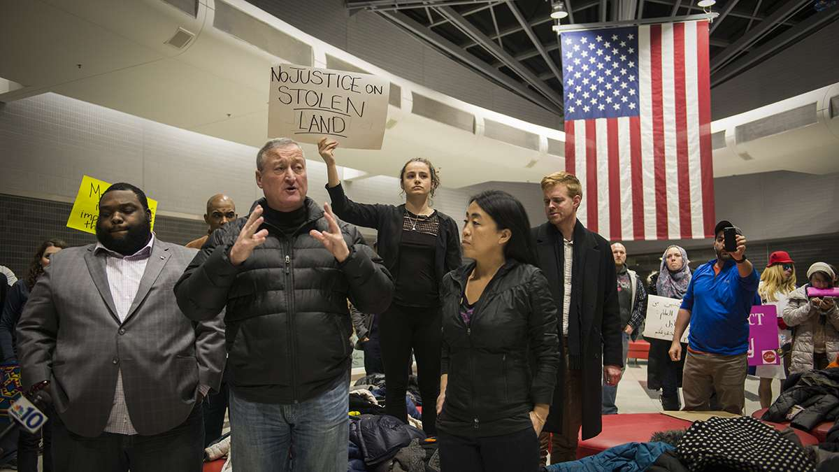 (From left) Rep. Jordan Harris, Philadelphia Mayor Jim Kenney, and Councilwoman Helen Gym speak to protesters and media about the developing situation regarding President Donald Trump's executive order on immigration at the Philadelphia International Airport. (Branden Eastwood for NewsWorks)