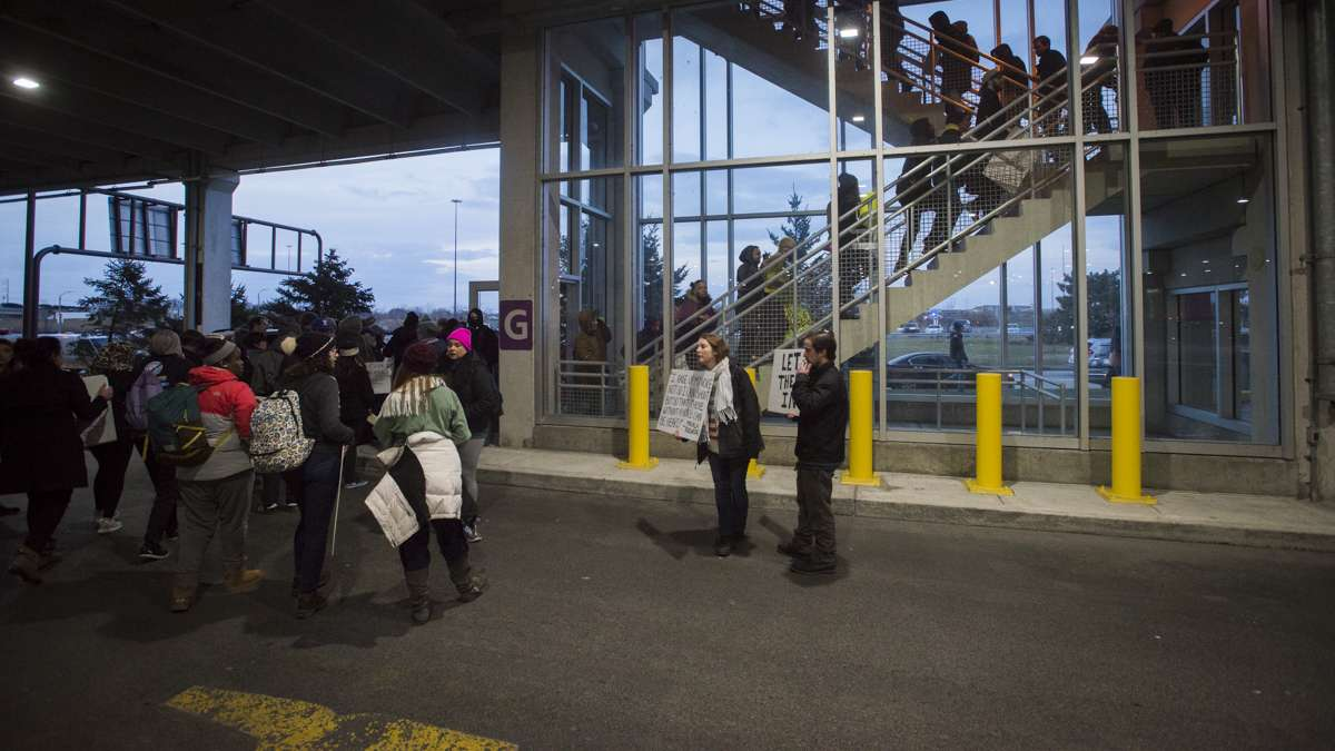 Protesters who had been denied entry into the terminal search for another way into the airport. (Branden Eastwood for NewsWorks)
