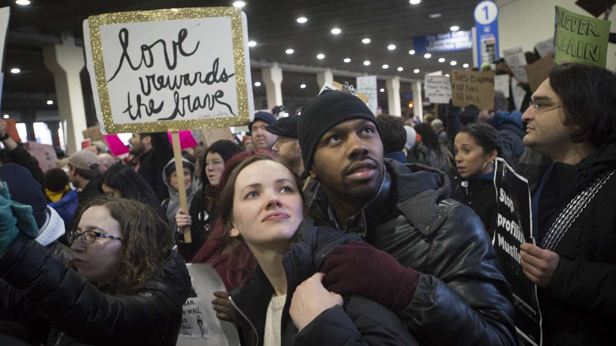 Leigh Wilson (left) and Nate Hall read signs at the protest against Donald Trump's executive order on immigration. Wilson says this is her fourth protest opposing Trump. (Branden Eastwood for NewsWorks)