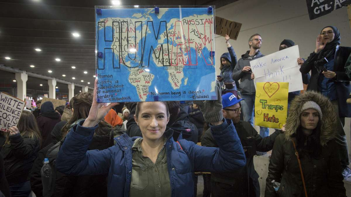 Ashley Woodruff of Philadelphia holds a sign she made over a year earlier in a class on immigration law at her university. (Branden Eastwood for NewsWorks)