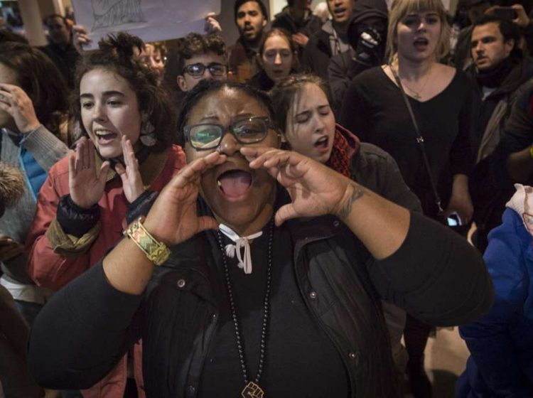 Protesters chant slogans inside the terminal at Philadelphia International Airport. (Branden Eastwood for NewsWorks)