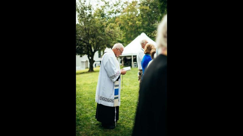 Father Martin Kobos prays a Living Rosary while holding his own Rosary given to him by Pope John Paul II.