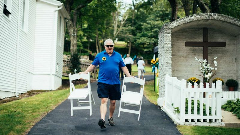 Mike Pesarchick, a member of Ss. Peter & Paul in Mount Carmel, brings chairs to accomidate more pilgims on the lawn during Divine Liturgy.