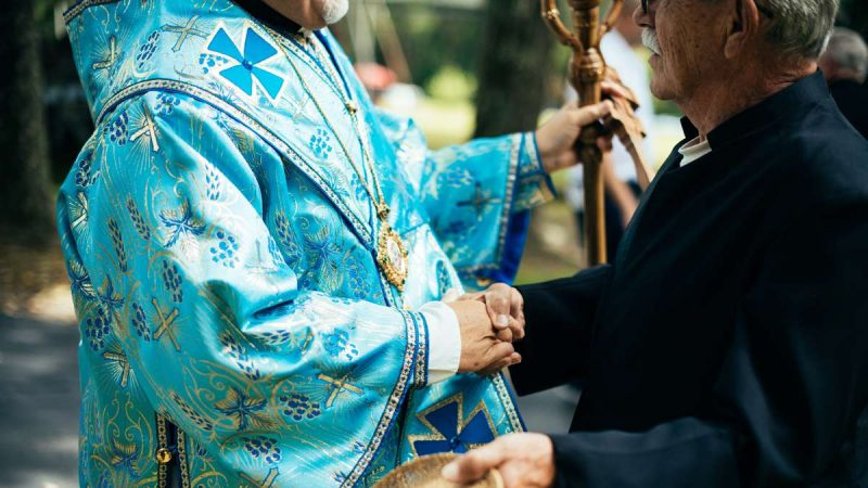 A man named Uriy (George) shakes hands with Metropolitan-Archbishop Stefan Soroka.