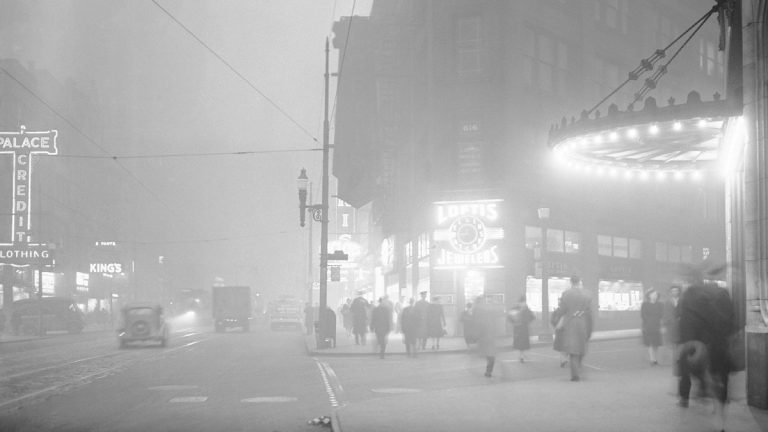 In this archival photograph from 1944, the clock at right center shows a quarter to noon, but in downtown Pittsburgh, Pa., residents walked in artificially lighted streets when one of the heaviest smogs in the city's history blanketed the town. Today, only two Pa. cities have air quality that is average or above average compared to other U.S. cities.(AP File Photo/Walter Stein)