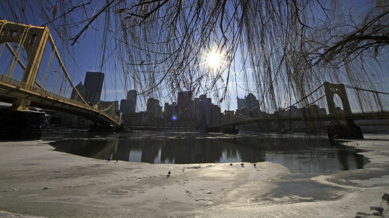The sun hangs over the skyline of downtown Pittsburgh, beginning to melt the ice on the Allegheny river. (AP Photo/Gene J. Puskar)