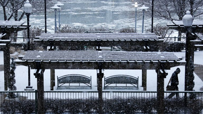 Snow falls on a park overlooking the Allegheny River in downtown Pittsburgh during evening rush hour Wednesday