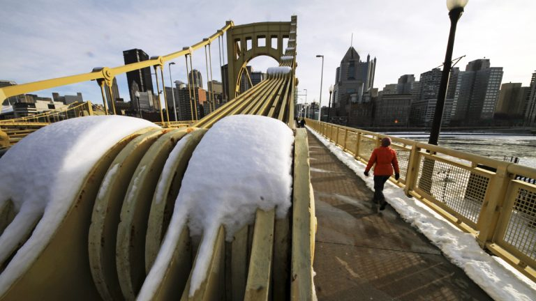 A woman walks across the Roberto Clemente bridge over the Allegheny River in downtown Pittsburgh. (AP Photo/Gene J. Puskar)