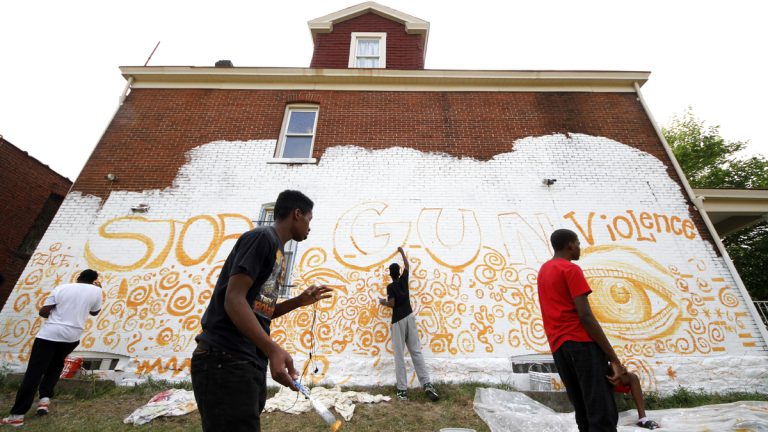 Young adult artists in the Homewood section of Pittsburgh paint a mural on the side of a building as part of a community wide 10 mural project organized by Moving the Lives through its Community Mural Project Wednesday, July 13, 2016. (AP Photo/Gene J. Puskar)