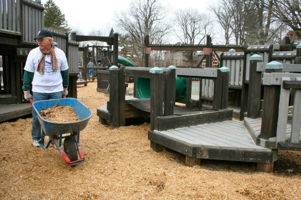 <p><p>A volunteer wheels mulch near playground equipment to be spread out. (Lane Blackmer/for NewsWorks)</p></p>