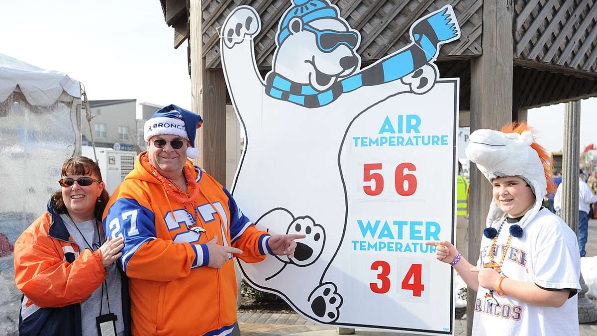 Some Broncos fans in a happier time on Super Bowl Sunday before the game pointing out the very mild air temperature at 56 degrees, compared to the chilly water temperature at 34 degrees. (Chuck Snyder/for NewsWorks)