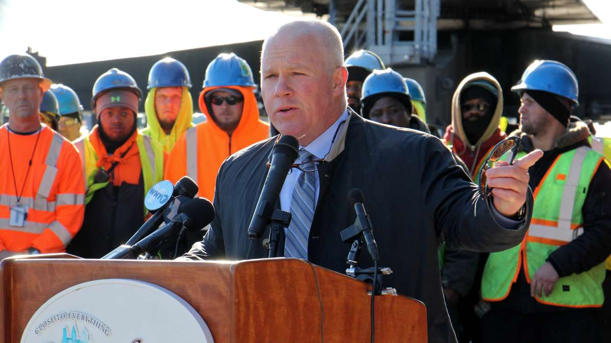 Leo Holt of Holt Logistics, which invested more than $12 million at the site, speaks as dozens of dock workers gather behind him. (Emma Lee/WHYY)