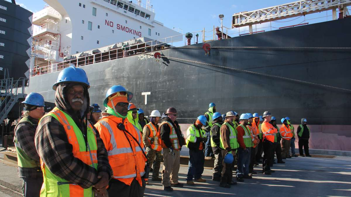 Dockworkers stand beside massive ship Doric Warrior, ready to unload its cargo of steel at the Paulsboro Marine Terminal. (Emma Lee/WHYY)