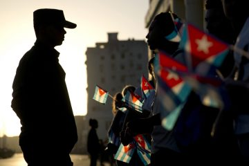 A soldier is silhouetted against the early morning sky as people holding Cuban flags wait for the motorcade transporting the remains of Cuban leader Fidel Castro in Havana, Cuba, Wednesday, Nov. 30, 2016. Castro's ashes have begun a four-day journey across Cuba from Havana to their final resting place in the eastern city of Santiago. (AP Photo/Natacha Pisarenko)