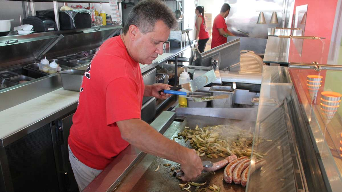 John Spadavecchia throws some onions and sausages on the griddle at Johnny Fries in Ortley Beach. The restaurant is doing a brisk business serving the contractors who are working overtime to repair Sandy damage. (Emma Lee/for NewsWorks)