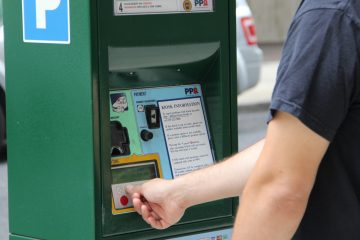 A man buys parking time at a kiosk on Filbert Street. (Emma Lee/WHYY, file)