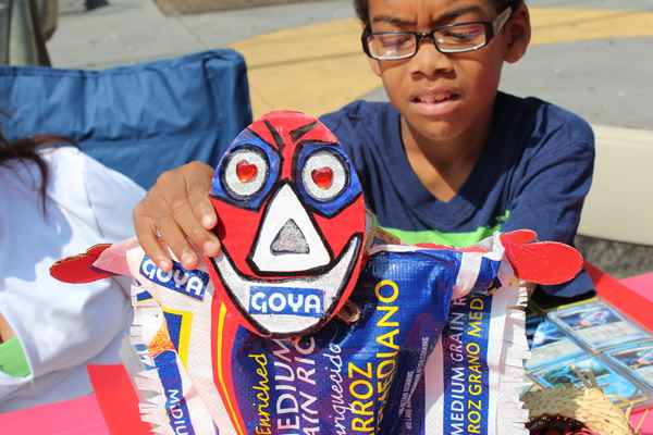 "Johnny shows his grandmother's work. As a visual artist and educator, Andria Morales uses recycled materials, in this case a Goya rice bag, to create small ""Vejigantes"", traditional Puerto Rican masks.  (Elisabeth Perez-Luna/WHYY)"