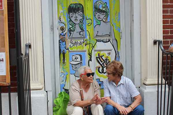A conversation among friends at the foot of two graffiti women. (Elisabeth Perez-Luna