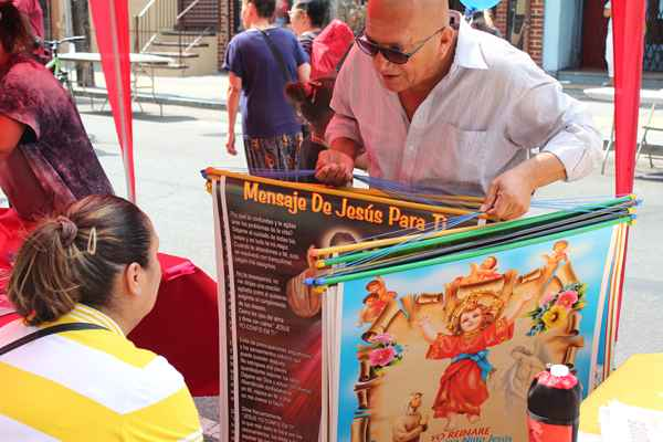 I caught up with this man as he walked the length of the festival peddling colorful posters targeted to any religious belief preference.  When the vendor ran out of posters, he switched to selling Latino themed t-shirts. Real entrepreneur!  (Elisabeth Perez-Luna/WHYY)