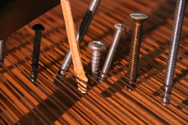 <p>Bolts and screws of various types and sizes, pieces of wood and bits of rubber are arranged among the strings of a grand piano at the Philadelphia Art Museum according to composer John Cage's specific instructions. (Emma Lee/for NewsWorks)</p>