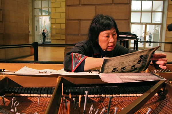 <p>Margaret Leng Tan consults the instructions for preparing a piano for a John Cage Competition. Bolts, screws, and bits of wood and rubber are arranged among the strings. (Emma Lee/for NewsWorks)</p>